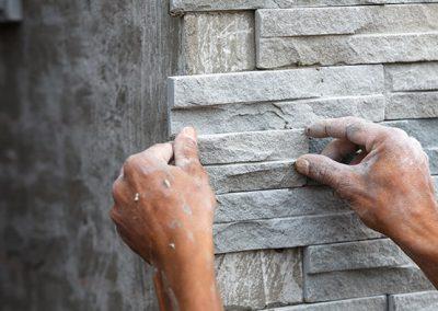 Contractor applying granite wall veneers to exterior of institutional building.