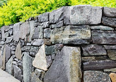 Mismatched Muskoka granite used to create a strong retaining wall outdoors.