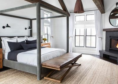 Warm bedroom accompanied with a black granite fireplace.