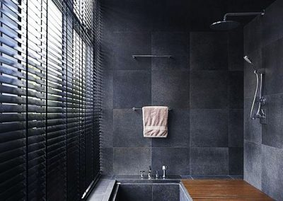 Contemporary bathroom with large granite tiles used for flooring and extended wall coping.